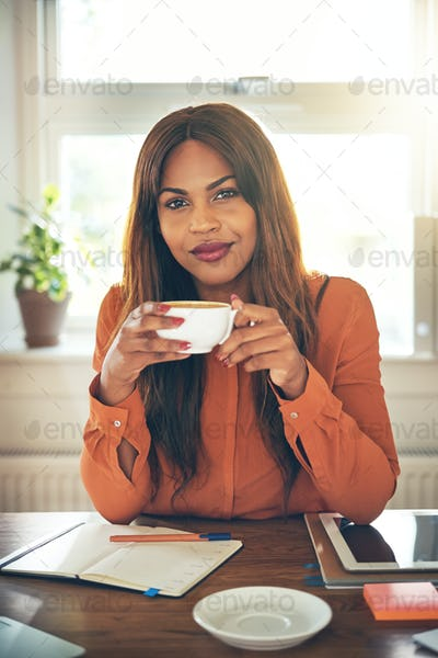 Confident young female entrepreneur drinking coffee while working from home