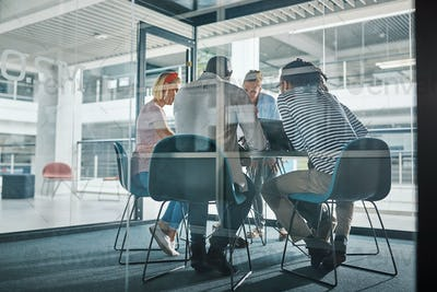Diverse businesspeople meeting inside of a glass walled office boardroom