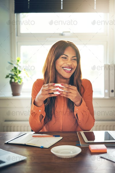 Smiling young entrepreneur drinking coffee while working from home