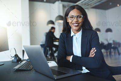 Confident young African American businesswoman sitting at her office desk