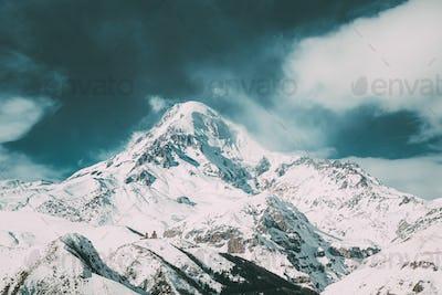 Stepantsminda, Gergeti, Georgia. Peak Of Mount Kazbek Covered With Snow.