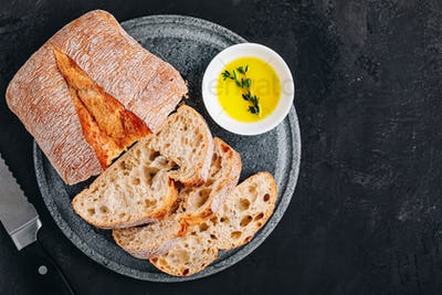Italian ciabatta bread slices with olive oil on stone plate on dark concrete background