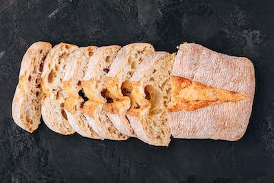 Italian ciabatta bread slices on dark stone concrete background