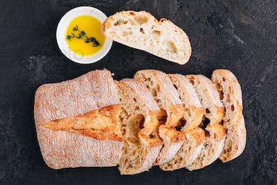 Italian ciabatta bread slices with olive oil on dark stone concrete background