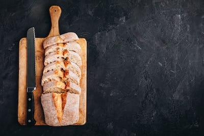 Italian ciabatta bread slices on wooden chopping board on dark stone concrete backdrop