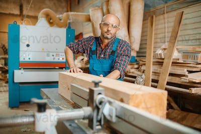 Carpenter processes wooden beam on plane machine