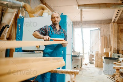 Carpenter processes board on plane machine