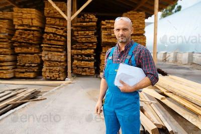 Carpenter in uniform check boards on sawmill