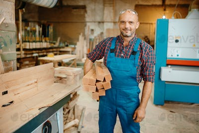 Carpenter holds stack of wooden beams, carpentry