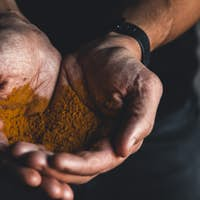 Turmeric in hand With black background. medicine. food supplement