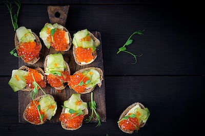 Canape with salmon red caviar. Sandwich for lunch. Delicious food. Top view, overhead