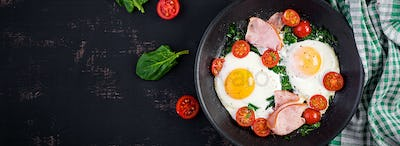 Keto diet food. Fried egg, ham, spinach, and tomatoes. Keto, paleo breakfast. Top view, banner