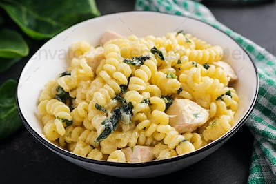 Fusilli pasta with a creamy sauce with chicken meat, parmesan cheese and spinach on a bowl