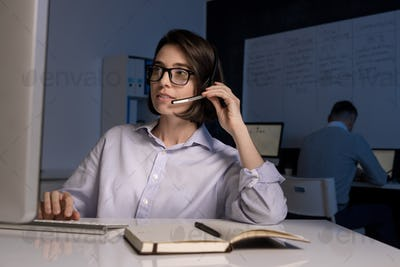 Young female hotline operator with headset speaking to clients online