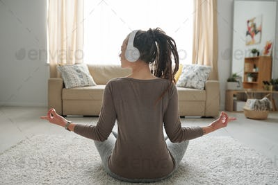 Girl listening to relaxing music in headphones while sitting in pose of lotus