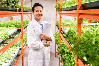 Young successful female researcher or agronomist in whitecoat standing in aisle