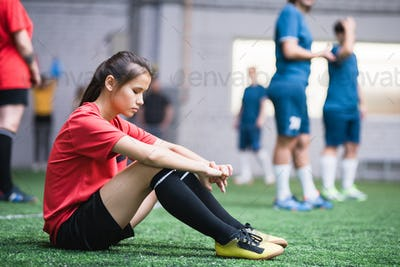 Sad or tired female football player in sports uniform sitting on green field