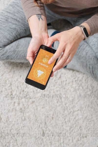 Overview of active female hands holding smartphone over floor