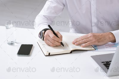 Hands of employer with pen over page of notebook writing down plan for the day