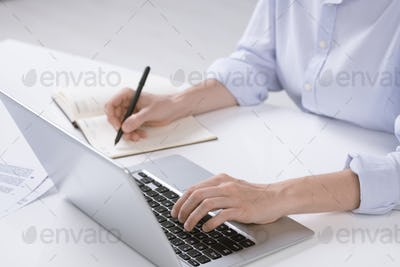 Hand of young businesswoman pushing keys of laptop keypad while making notes
