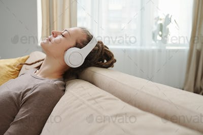 Young serene female with headphones enjoying music for relax on couch