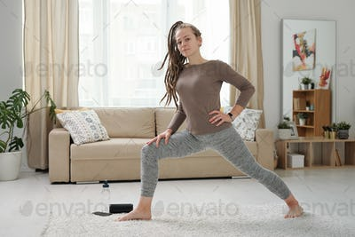 Young barefoot woman in leggins and pullover stretching legs during exercise