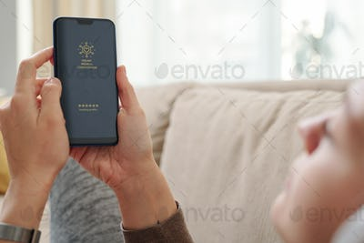 Hands of restful girl with smartphone going to get online medical consultation