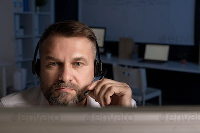 Confident customer support representative with headset speaking in microphone