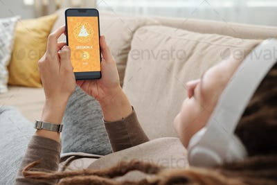 Hands of restful female with smartphone waiting for uploading of website page