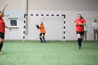 Young active sportswoman going to throw soccer ball to other player of her team