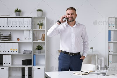 Successful mature entrepreneur in formalwear talking on smartphone to client