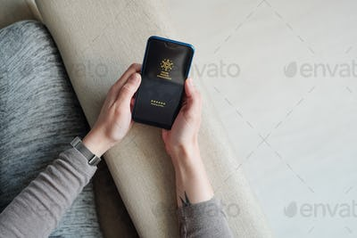 Hands of girl with mobile phone sitting on couch and waiting for loading profile