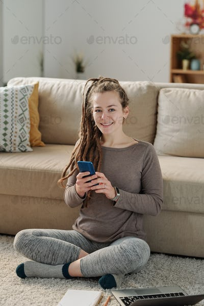 Happy young woman with smartphone sitting on the floor by couch