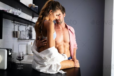 Attractive passionate couple is having sex on kitchen