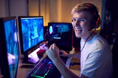 Teenage Boy Wearing Headset Gaming At Home Using Dual Computer Screens