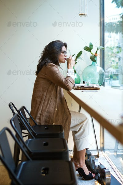 Beautiful young woman drinking Matcha green tea latte on wodden table in the coffee shop.