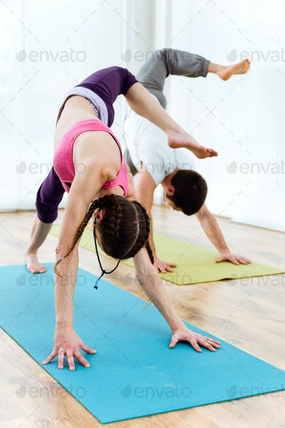 Beautiful young couple practicing yoga at home.