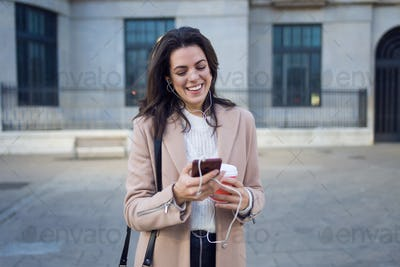 Pretty young woman using her mobile phone while holding cup of coffee in the street.