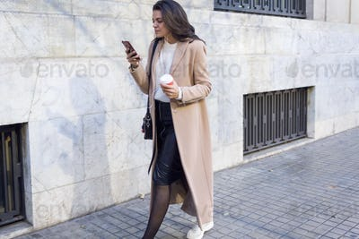 Pretty young woman using her mobile phone while walking in the street.