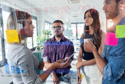 Successful business team discussing together in front of office glass board in the coworking space.
