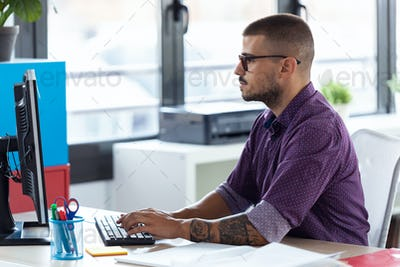 Software developer working with computer in the modern startup office.
