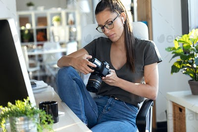 Professional young photographer reviewing the photos she has taken with the camera