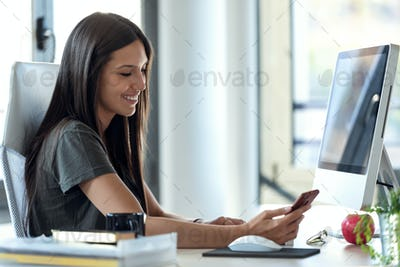Smiling young business woman using her mobile phone while working with computer in the office.