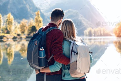 Two travel hikers in love enjoying the nature in front of the lake in mountain.