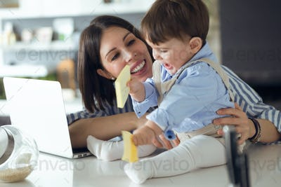 Pretty young mother with her baby playing with notebook at home.