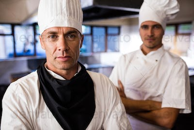 Two male chefs standing with arms crossed in kitchen