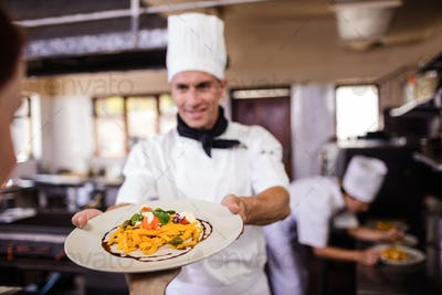 Male chef giving plate of prepared food to waitress in kitchen