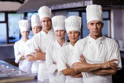 Group of chefs standing in kitchen