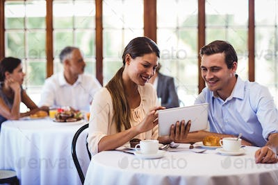 Couple discussing on digital tablet at table