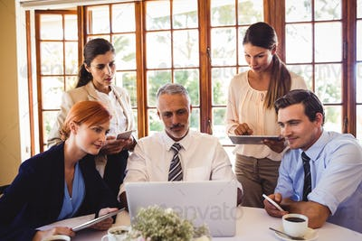 Business people discussing over laptop at table